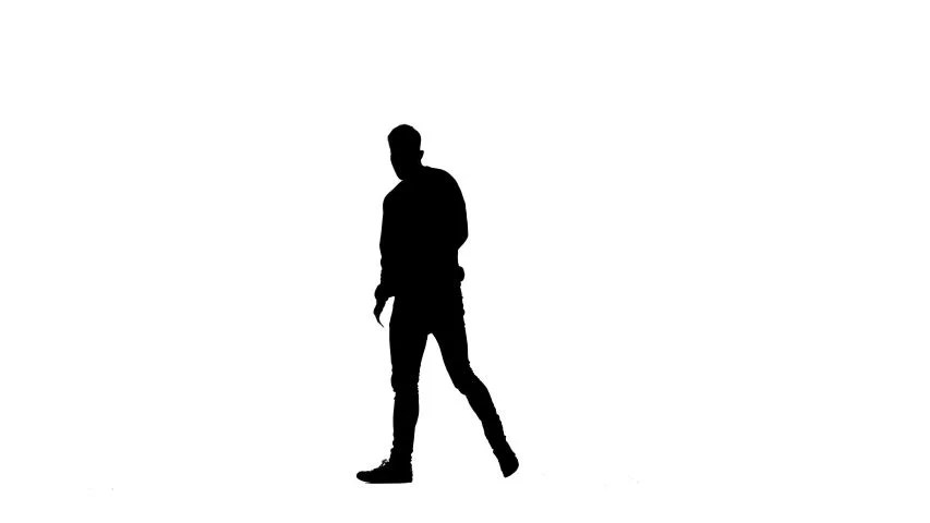 Silhouette of a young man walking with a backpack