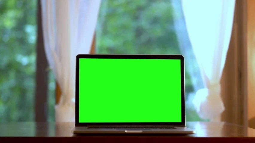 fast dolly push in to laptop computer with green screen on a table in front of windows with curtains concept for remote virtual distance learning
