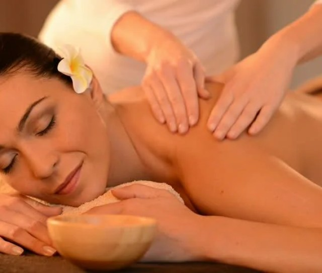 Relaxed Woman Receiving A Back Massage At Health Spa Latin Young Woman Lying On Massage Table Having A Massage With A Massage Oil