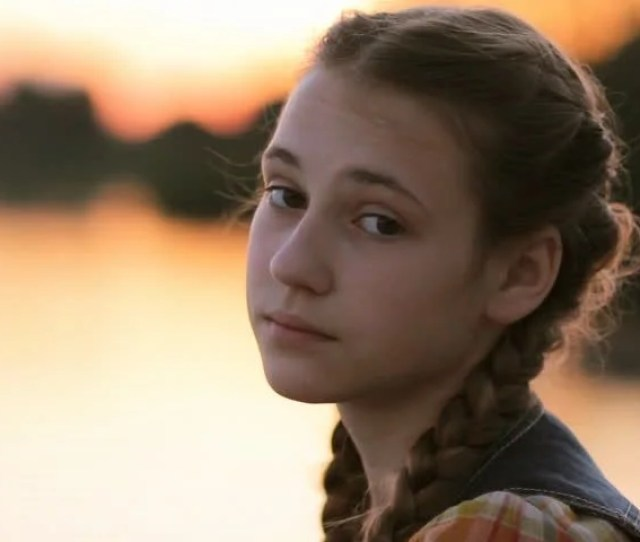 Teen Girl Face Serious Looking At Camera Portrait Of Pretty Young Girl 14 15 With Warm Sunset Colors On Calm Lake In The Background