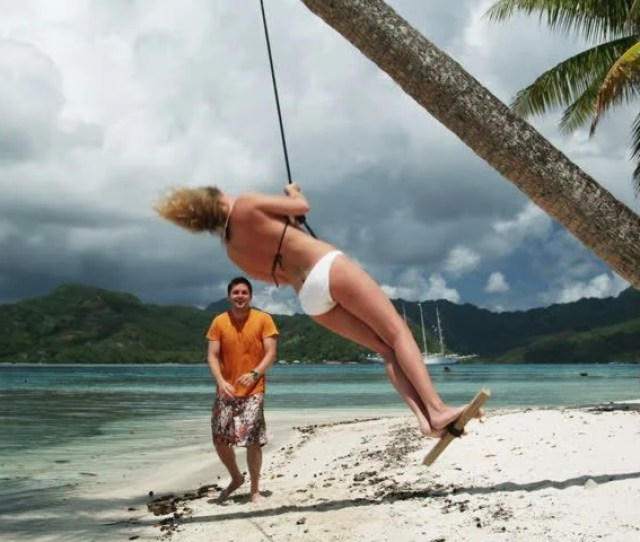 Couple Swinging On The Beach