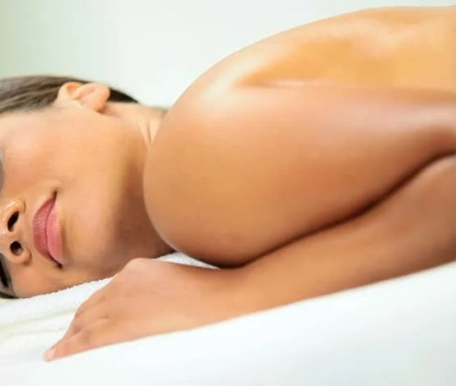Beautiful Ethnic Female Receiving Hot Stone Therapy Massage At Health Spa