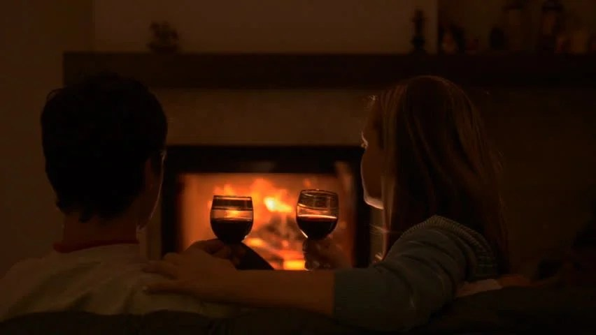 Couple Relaxing In Front Of Fireplace Man Looking At Woman Stock Couple Sitting On Sofa Kissing And Talking By The Fire