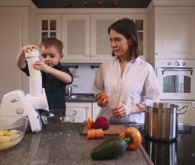 Mom Teaches His Son To Cook Food Boy Chopping Carrots In A Grinder