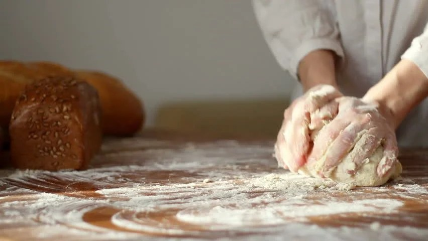 4 person kitchen table centerpiece ideas baker kneading dough in flour on table, slow motion, dolly ...
