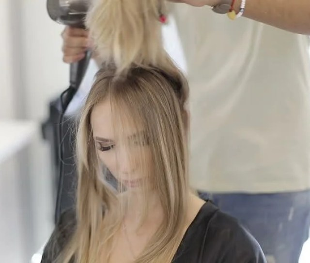 A Male Hairdresser Dries Long Hair Blonde Hair Drier In A Modern Beauty Salon Balayage