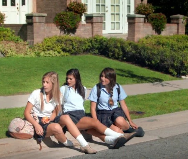 Three Pretty Uniformed Teen School Girls Waiting On A Curb