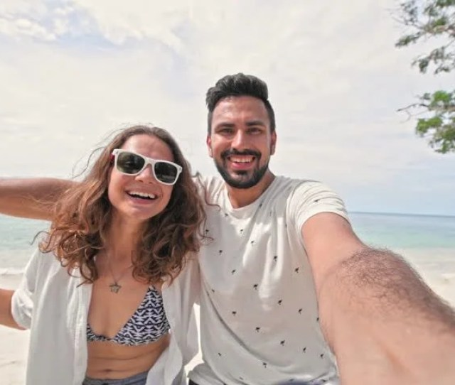 A Young Couple Swinging On A Swing And Shoot Themselves On Camera In A Tropical Beach Couple In Love On A Beach Swing By The Sea In Southeast Asia Selfie