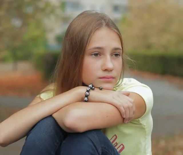 Sad Girl Depressed Cute Teen Female Sitting Deep In Thought With Head On Knees On Park Bench