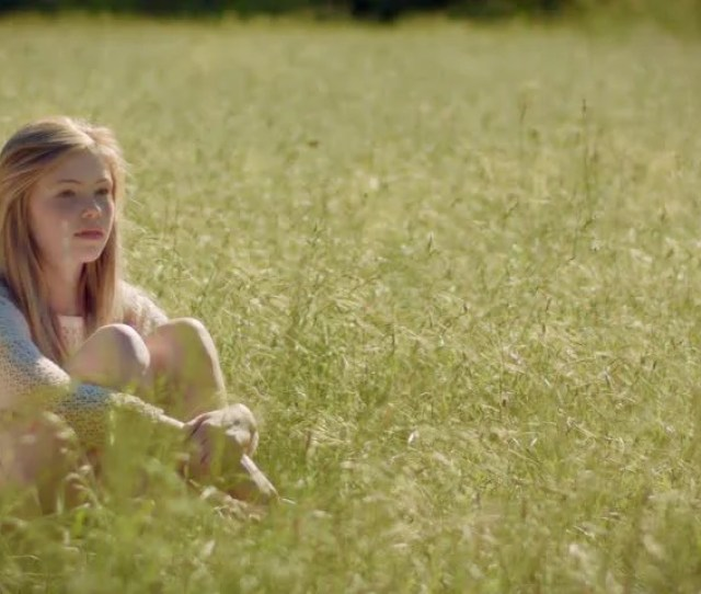 Pretty Blonde Teen Sits Alone In A Meadow She Looks Off Into The Distance Then Sweetly At Camera
