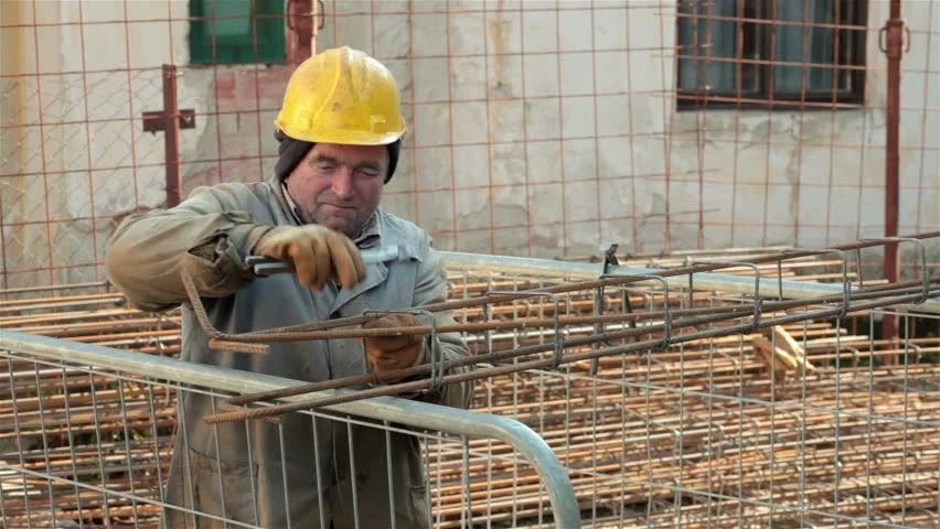 Construction Worker Wearing Helmet Using A Pliers To