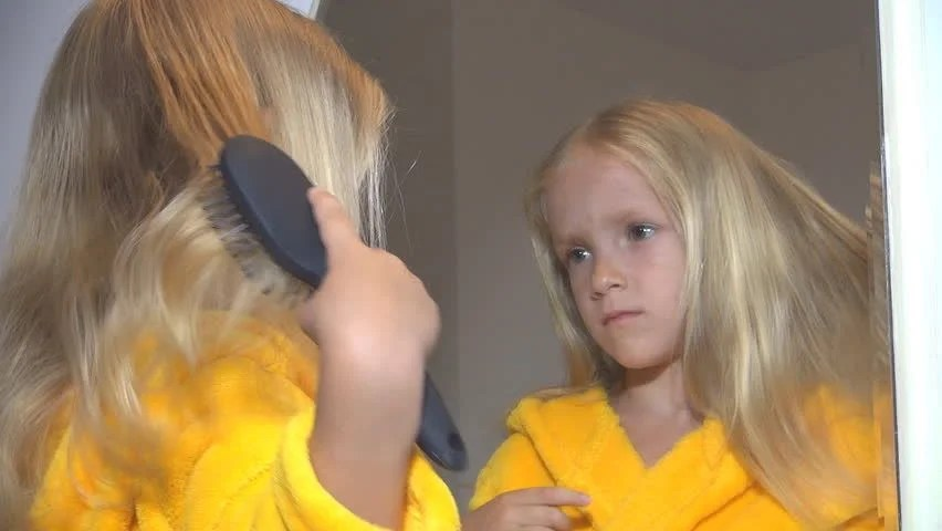child in bathrobe combing mirror
