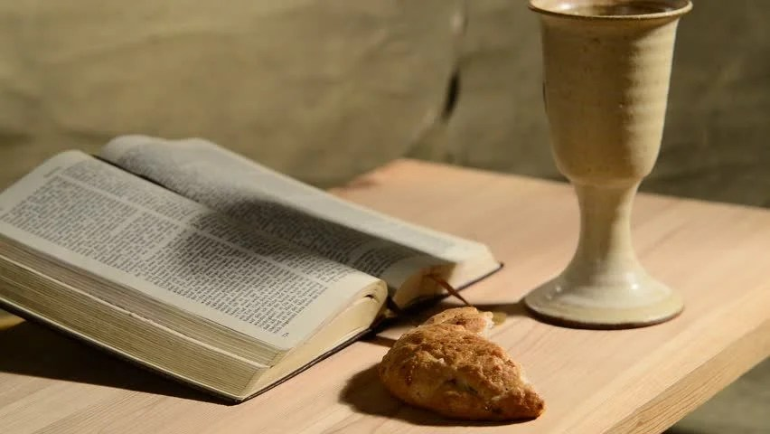 Stock video of bible with chalice and bread panning