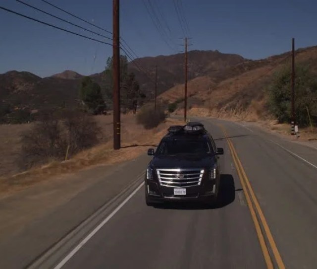 Day Moving Pov Shot Down Black Cadillac That Traveling Along Two Lane Mountain Road There Some Trees Bushes Some Mountains Background
