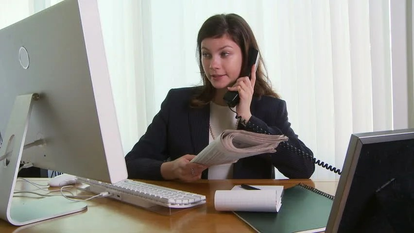 Young Business Woman At Desk With Phone And Computer Stock
