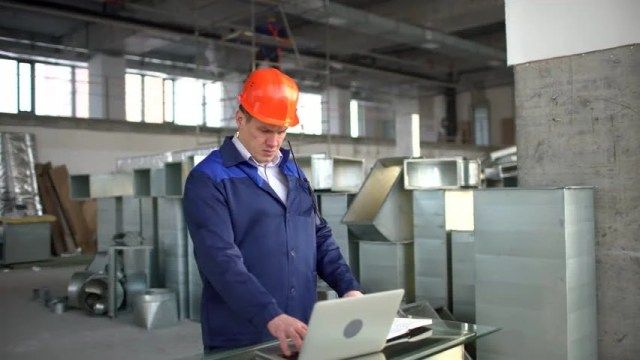 Factory Worker In A Hard Hat Is Using A Laptop Computer With An Engineering Software 4 K Engineer In Hard Hats Having Conversation Laptop Computer