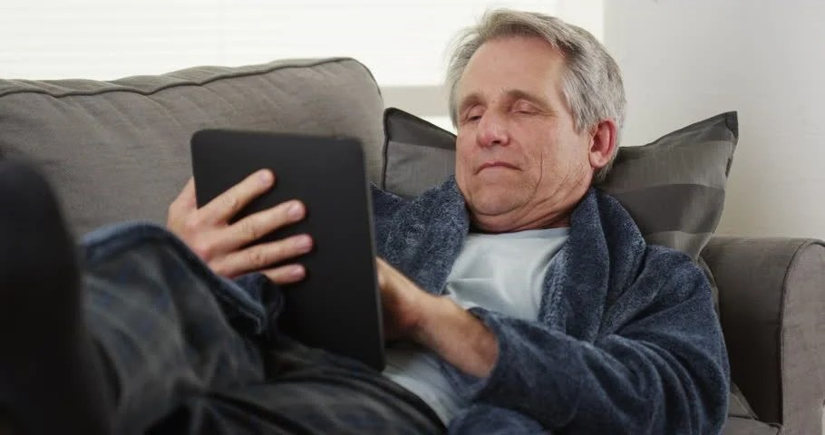 Man Relaxing With His Tablet Sitting In Recliner Chair In