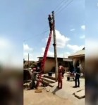 Angry Inhabitants Pull Electricity Official Off Ladder, Leaves Colleague Hanging On Pole