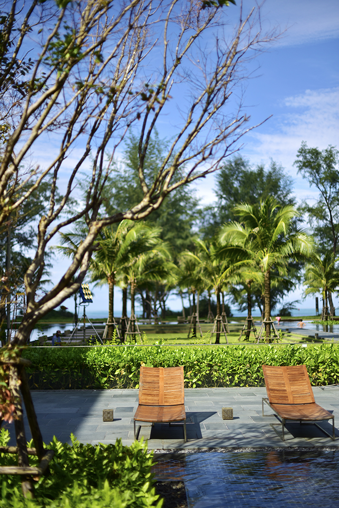Baan Mai Khao | Phuket | Akanksha Redhu | pool sun beds looking at beachside