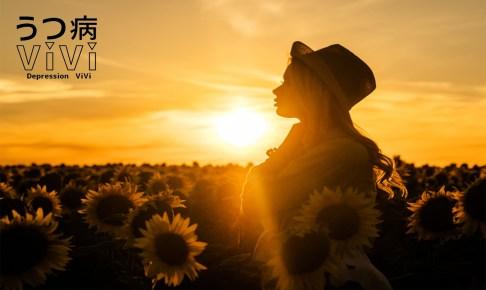 夕暮れのひまわり畑にたたずむ逆光の女性