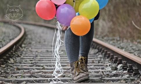 線路を風船を持って歩く女性