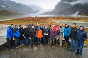 A group of scientists in rain gear gather for a group photo in front of a glacier in Southeast Alaska.