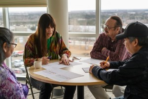 a group of workshop participants sit at a table writing