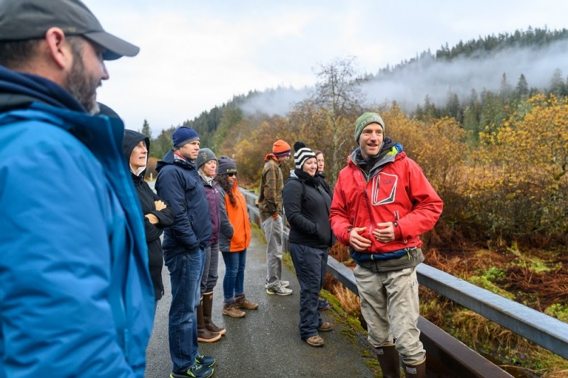 Man in red jacket speaking to a group of scientists gathered around him in front of a valley of trees in autumn colors.