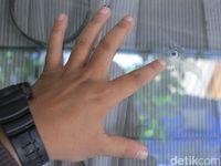 Warga memperlihatkan kaca rumahnya yang bolong ditembus peluru.