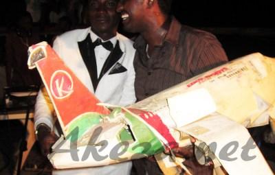 Yoya avec Mr Happy tenant le symbole de son ticket d'avion pour la Belgique (www.akeza.net)