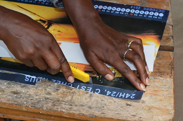 Calénie Nikundanya  en train de couper un morceau sur la page du calendrier, véritable matière première pour son travail afin de montrer le processus de l'opération.(www.akeza.net)