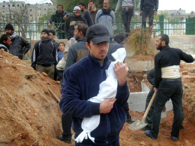 egyéves kisfiú teteme egy férfi kezében, aki éhen halt egy damaszkuszi menekült táborban