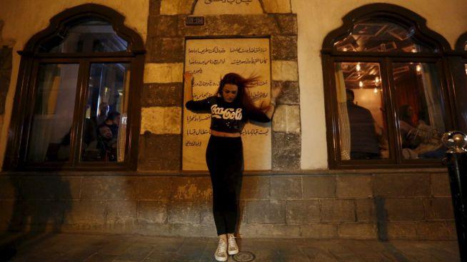 Fiatal nő pózol fényképezkedik a Beit Zaman hotel előtt Damaszkuszban