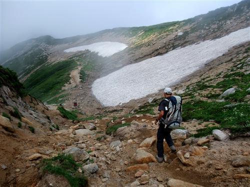 雪渓が残る稜線を行く