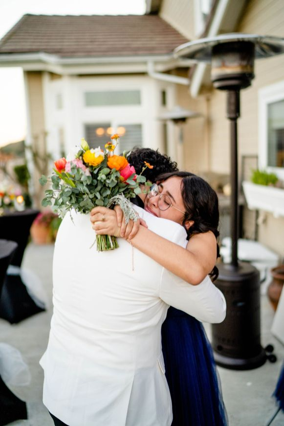 sister and groom hug