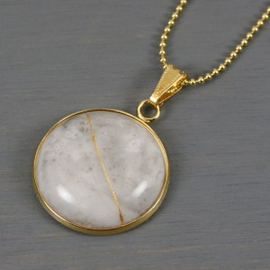 Crazy lace agate round kintsugi pendant in a gold setting on chain