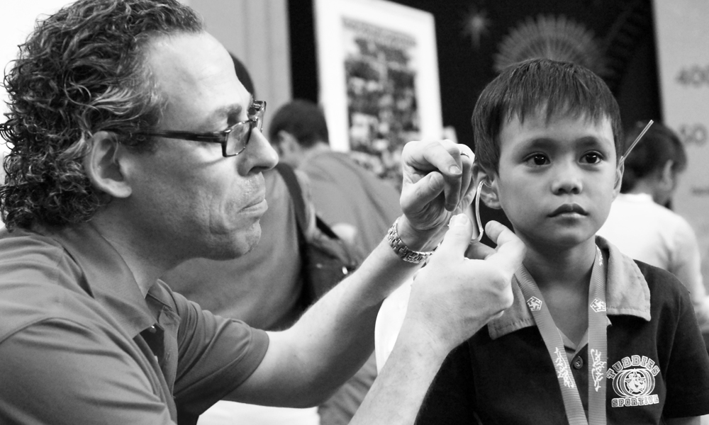 Bill Schiffmiller fitting a hearing aid for a Filipino child in need.