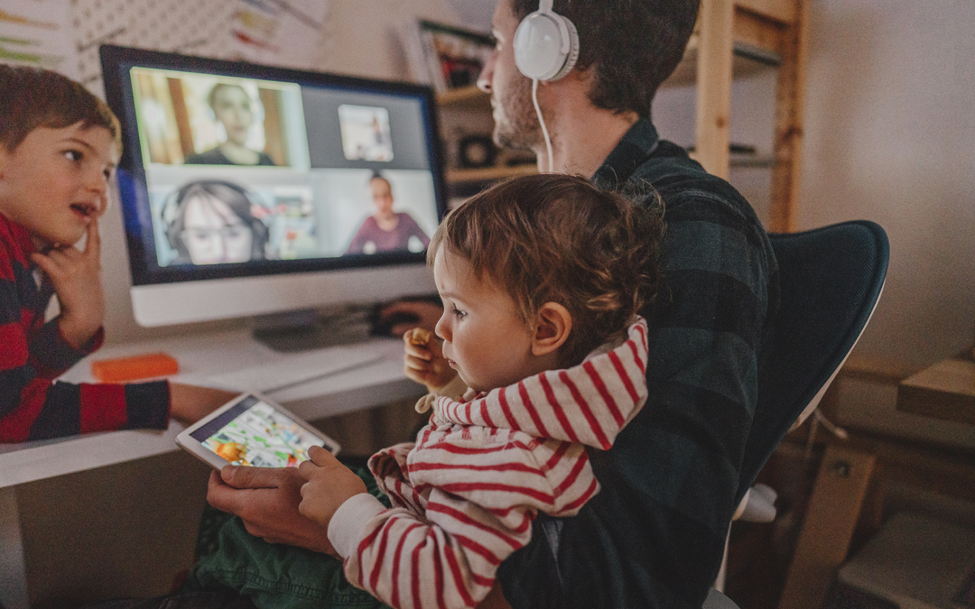 A young father attends an online meeting using headphones while entertaining two children.