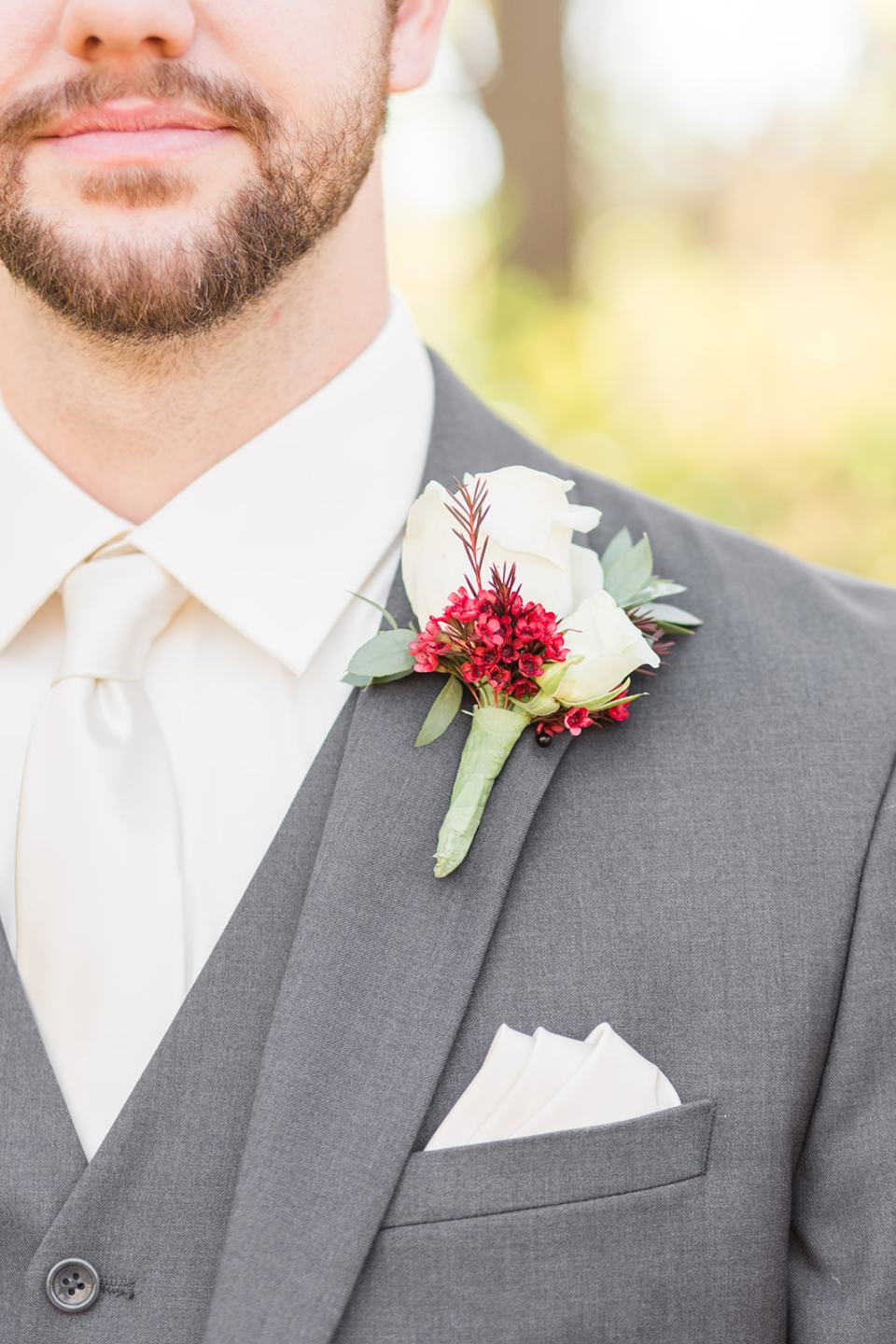 A groom with a white tie and white and red wedding boutonnieres