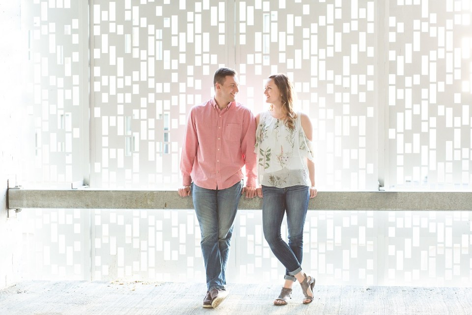 A couple wears a mix of pink, florals, and jeans for their Downtown Fargo engagement session