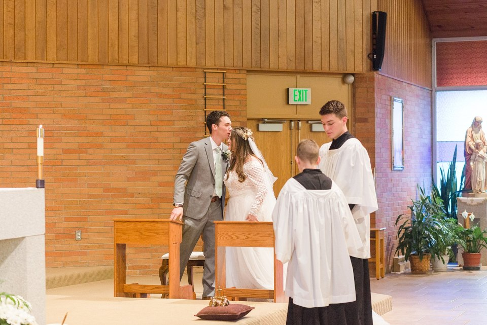 A groom kisses his bride on the forehead during their catholic wedding ceremony