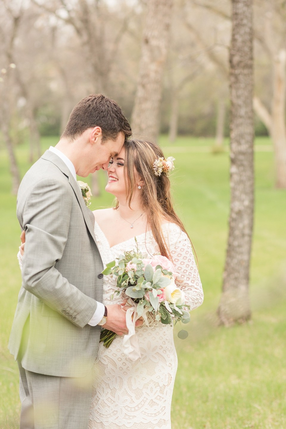 A bride and groom rest their foreheads together at the North Dakota Capital Grounds