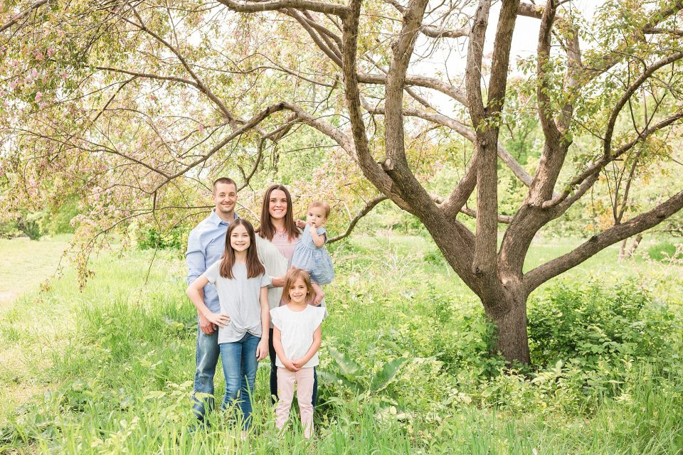 Family of five under blooming spring tree