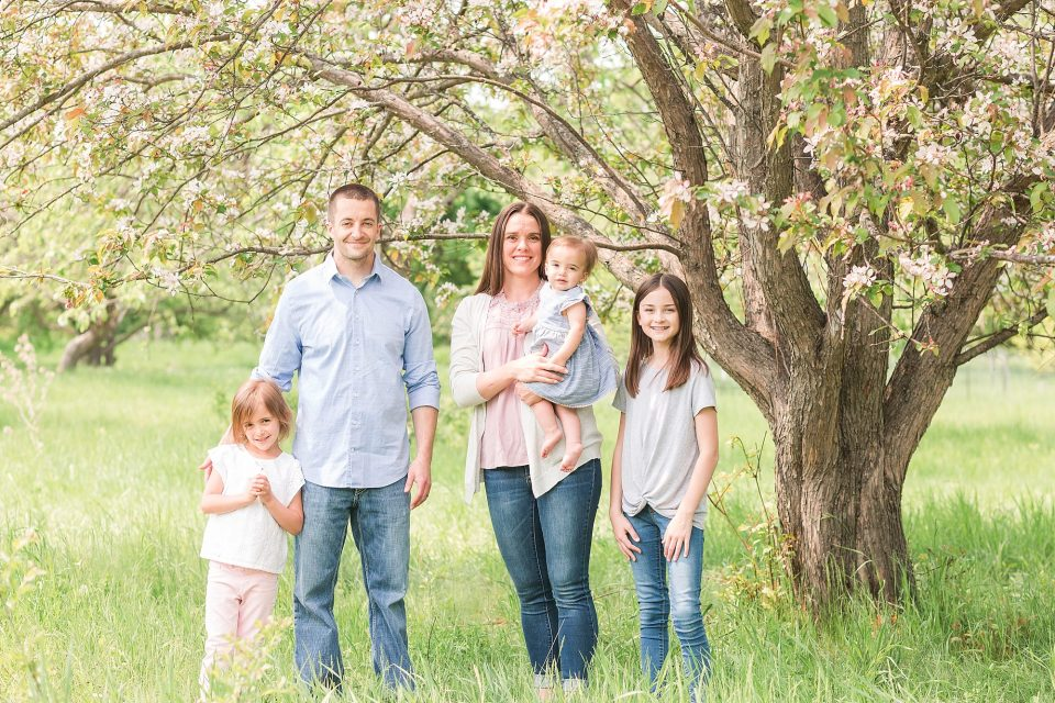 A couple smile with their three daughters for spring photos in orchard glen