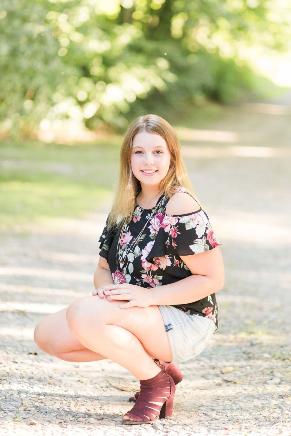 During a Lakeside Senior Portrait Session, a girl crouches down in maroon heels and a floral shirt.