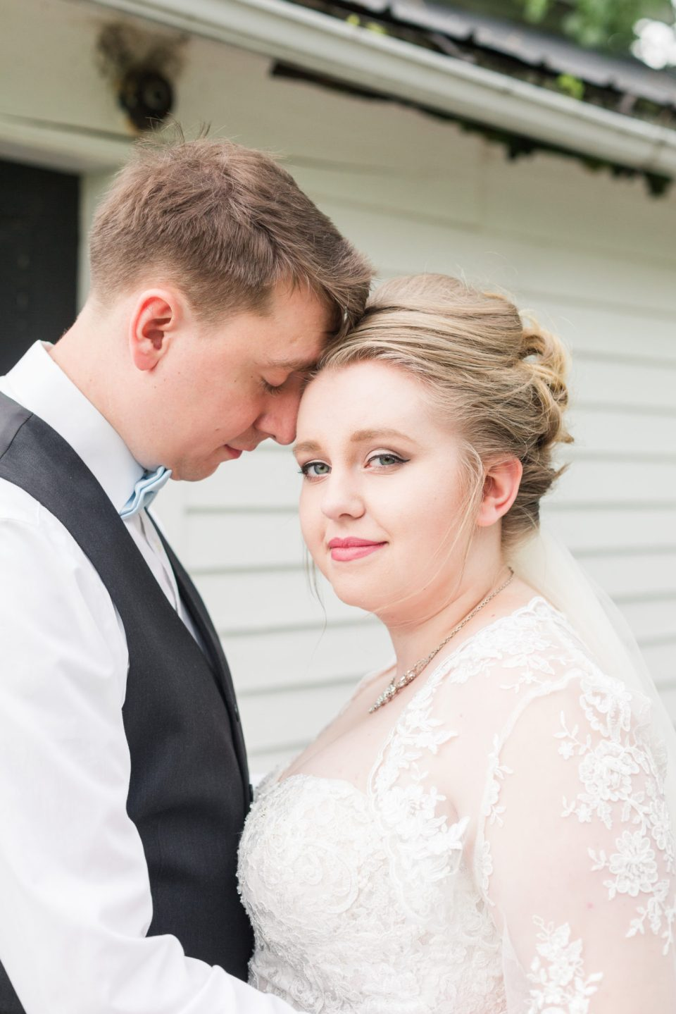 A bride smirks at the camera in a lace dress at A Friend's House