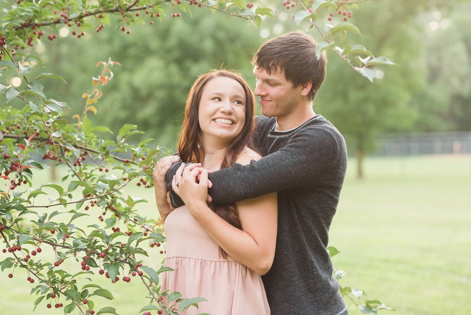 A couple smile at each other near a berry tree during their elmwood park engagement session