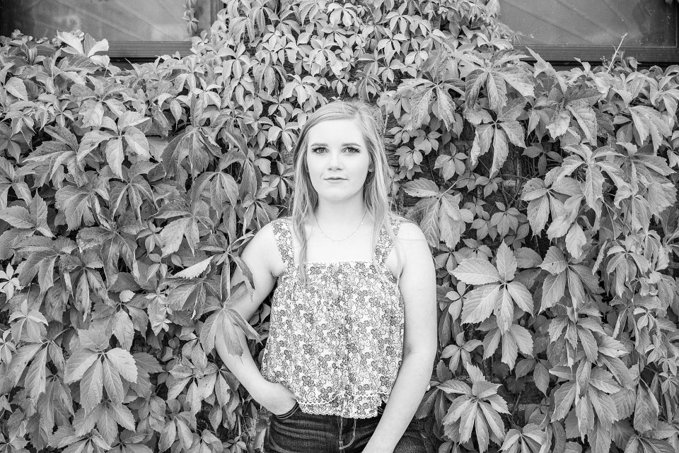 black and white Senior Portraits in Fargo against ivy wall