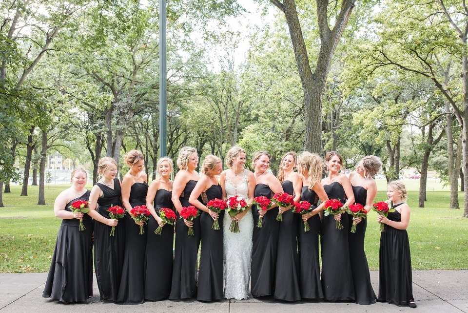 Bridesmaids in black glamorous dressed hold red rose bouquets