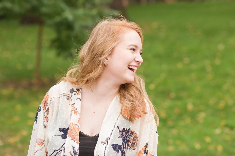 Senior girl laughs over her shoulder during her senior photo session in Fargo